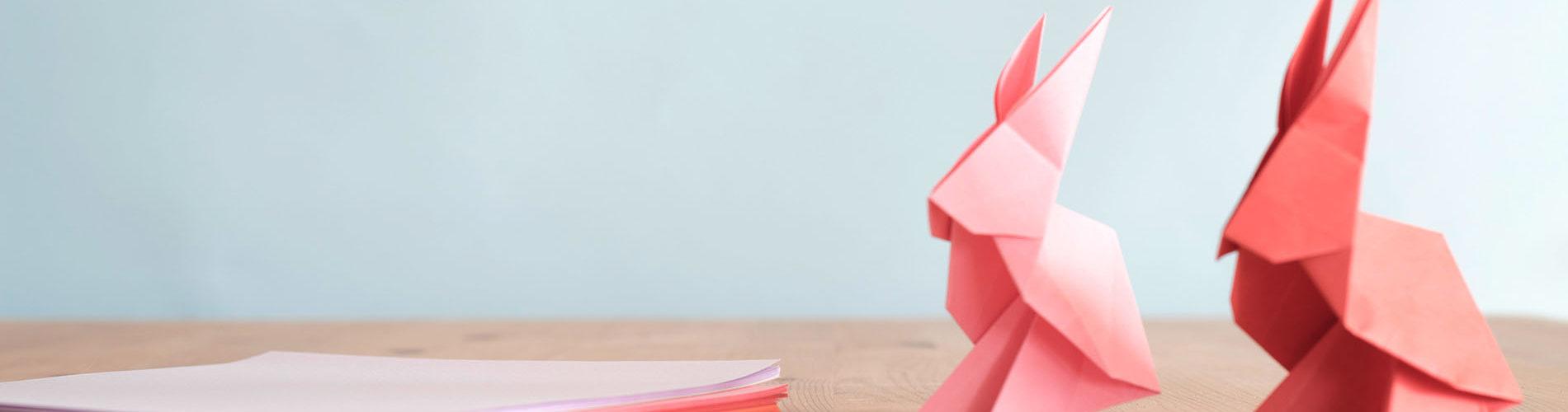 Origami rosa Hasen auf Schreibtisch
