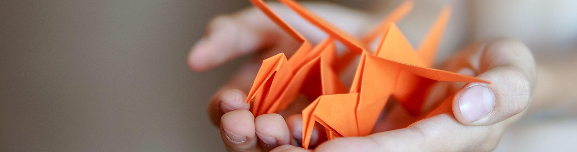 Origami Kraniche auf Hand
